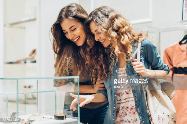 young women looking at golden jewelry in the mall - luxury girl stock photos and pictures