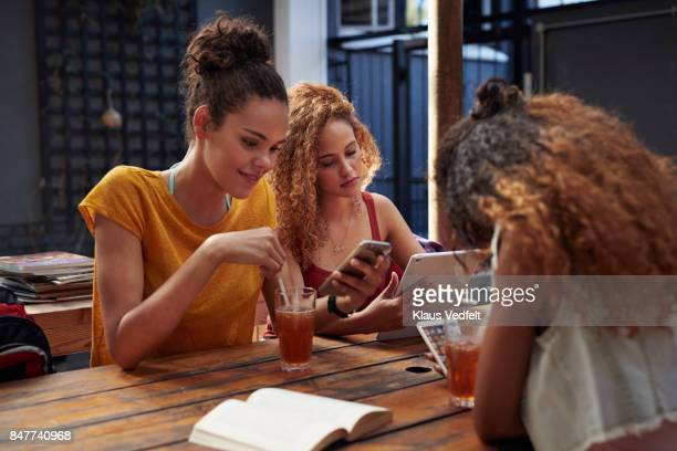 Young women looking at their own different phones and tablet