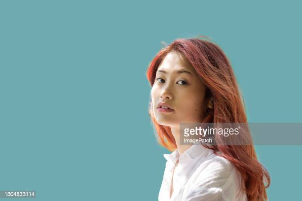 young women looking at viewer on plain coloured background - dyed red hair stock pictures, royalty-free photos & images