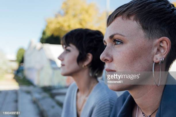 young women looking away while sitting outdoors - blank expression stock pictures, royalty-free photos & images