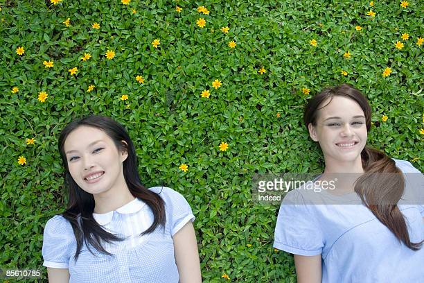 Young women lying down on field, smiling