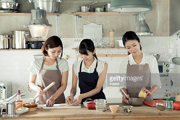 Young women making cookies in kitchen