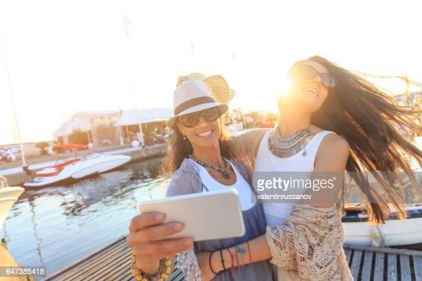 Young women making selfie on harbor