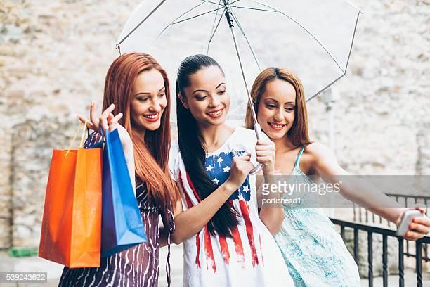 Junge Frauen, die selfie mit Sonnenschirm und Einkäufe