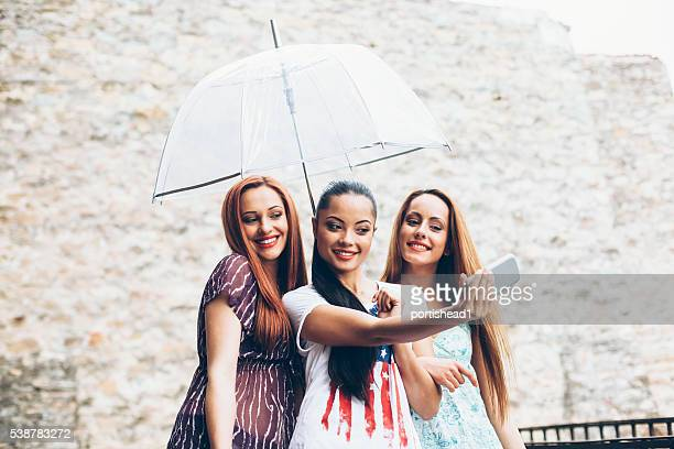 Young women making selfie with umbrella