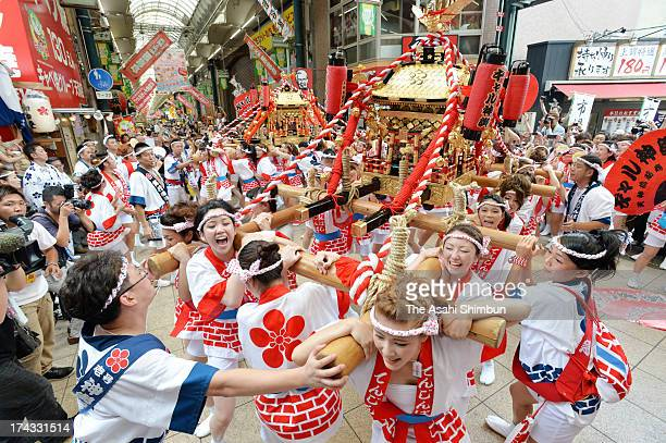 Young women march on with carrying portable shrines on the Tenjinsuji Shopping Street during 'Gal Mikoshi' ahead of the tenjin Festival on July 23...