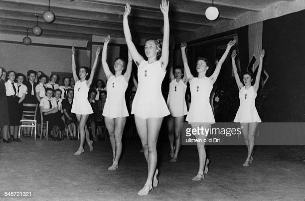 Young women of the 'Faith and Beauty Society' and employees of a department store are doing gymnastics