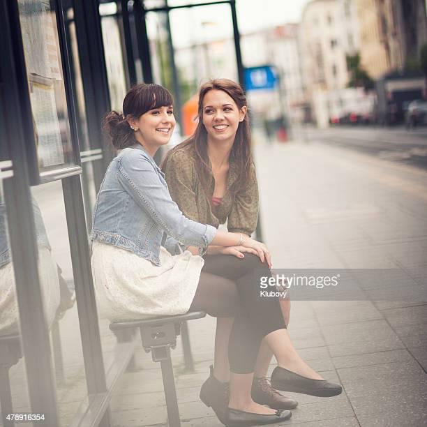 Junge Frauen auf eine Bushaltestelle