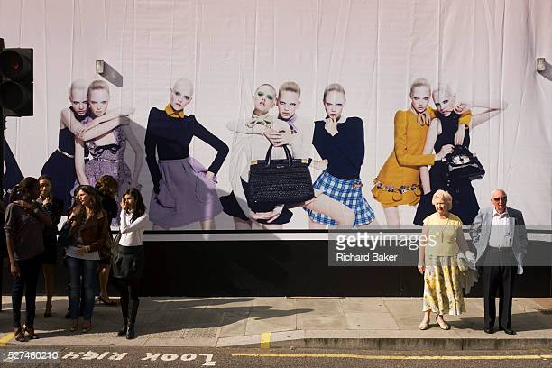 Young women on a shop hoarding with pedestrians and an elderly couple about to cross Brutoin Street in central London An image of young and older...