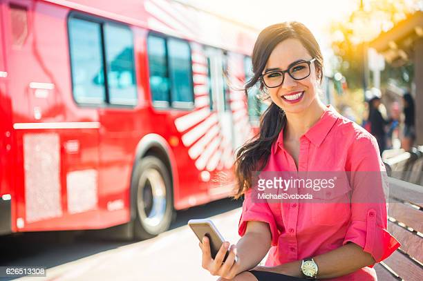 Young Women On Her Cell Phone At A Bus Stop