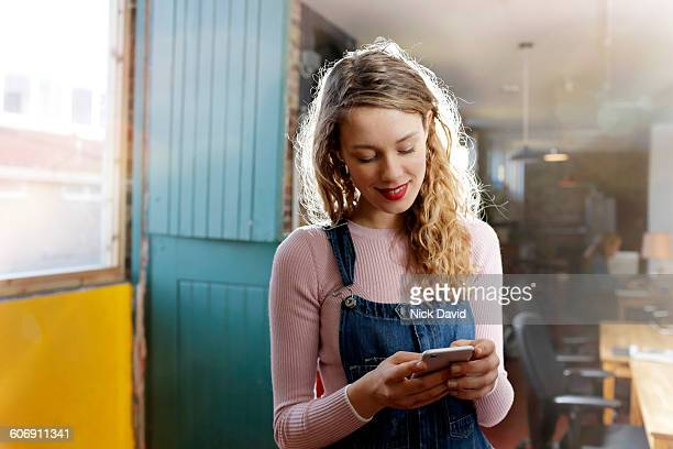 young women on her mobile phone in studio - genesis stock pictures, royalty-free photos & images