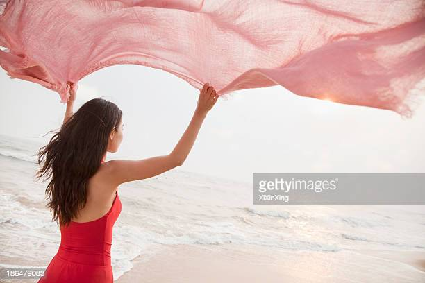 young women on the beach holding scarf in the air and looking into the distance - pañuelo rojo fotografías e imágenes de stock