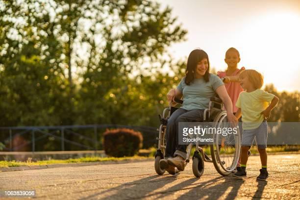 夕暮れ時の子供と歩いて車椅子で若い女性 - 麻痺 ストックフォトと画像