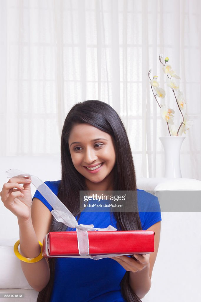 Young WOMEN opening a present : Stock Photo