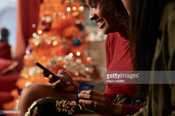 young women ordering christmas gifts online with creditcard - gemak stockfoto's en -beelden