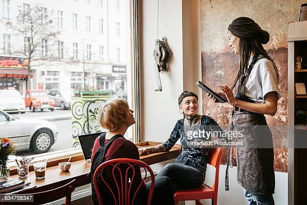 Young women ordering something in a café
