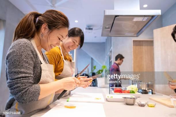 jonge vrouwen peeling groenten bij het koken van de school - alleen volwassenen stockfoto's en -beelden