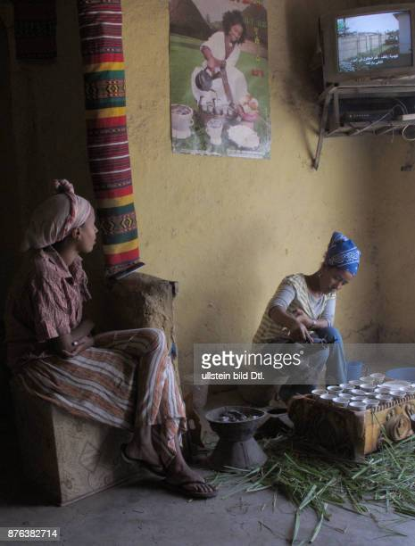 Young women performing a traditional coffee ceremony with TV on in a village in Ethiopia