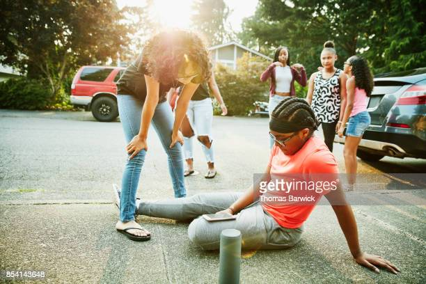 Young women picking music on smartphone while hanging out with friends on summer evening