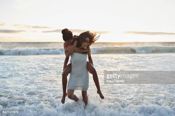 young women piggybacking in the water on beach - lesbienne photos et images de collection
