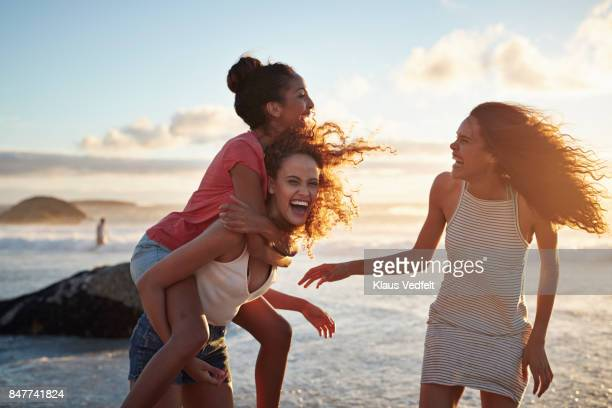 young women piggybacking on sandy beach - spaß stock-fotos und bilder