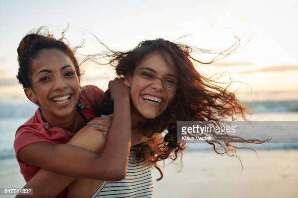 young women piggybacking on sandy beach - friends stock pictures, royalty-free photos & images