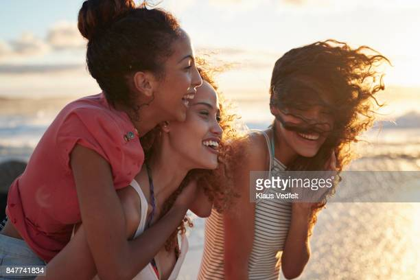 Young women piggybacking on sandy beach