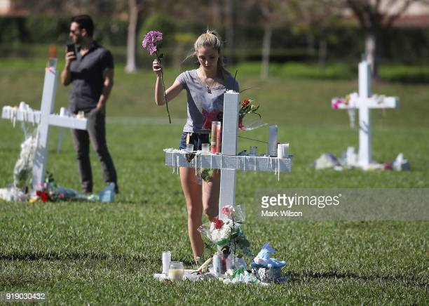 A young women places flowers at a memorial site that honors victims of the mass shooting at Marjory Stoneman Douglas High School at Pine Trail Park...