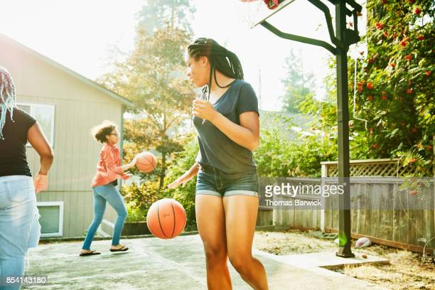 Young women playing basketball in backyard on summer afternoon