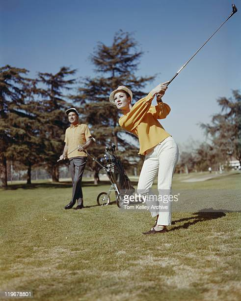 Young women playing golf while man standing in background