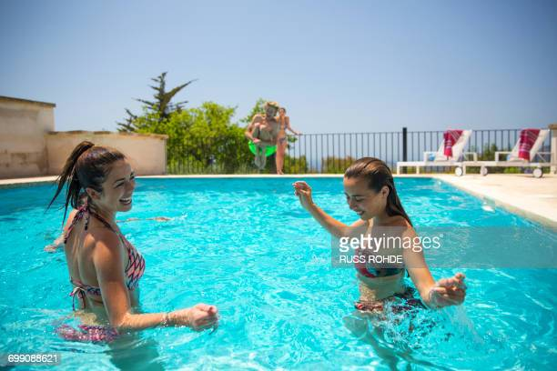 Young women playing in boutique hotel swimming pool, Majorca, Spain