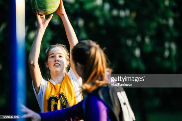 young women playing netball on outdoor court