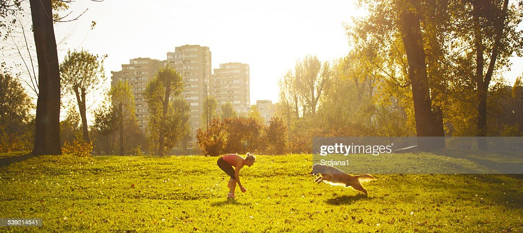 Young women playing with her dog : Stock Photo