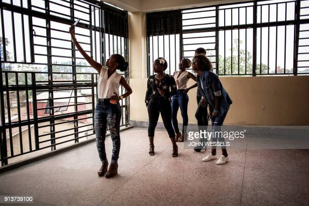 TOPSHOT Young women pose for a group selfie ahead of a welcoming ceremony for first year students on February 3 2018 in Beni / AFP PHOTO / JOHN...