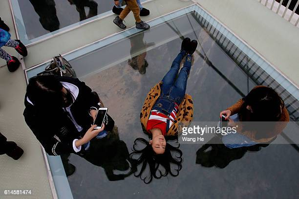 Young women pose for pictures on the glassfloor suspension bridge in Zhangjiajie in south China's Hunan province on October 14 2016 in Zhangjiajie...