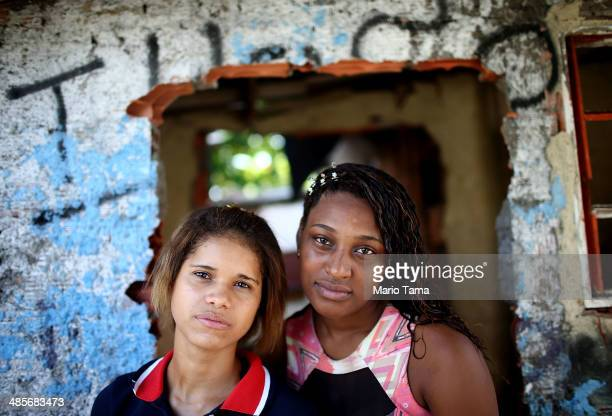 Young women pose in the occupied Complexo da Mare one of the largest 'favela' complexes in Rio on April 19 2014 in Rio de Janeiro Brazil The...