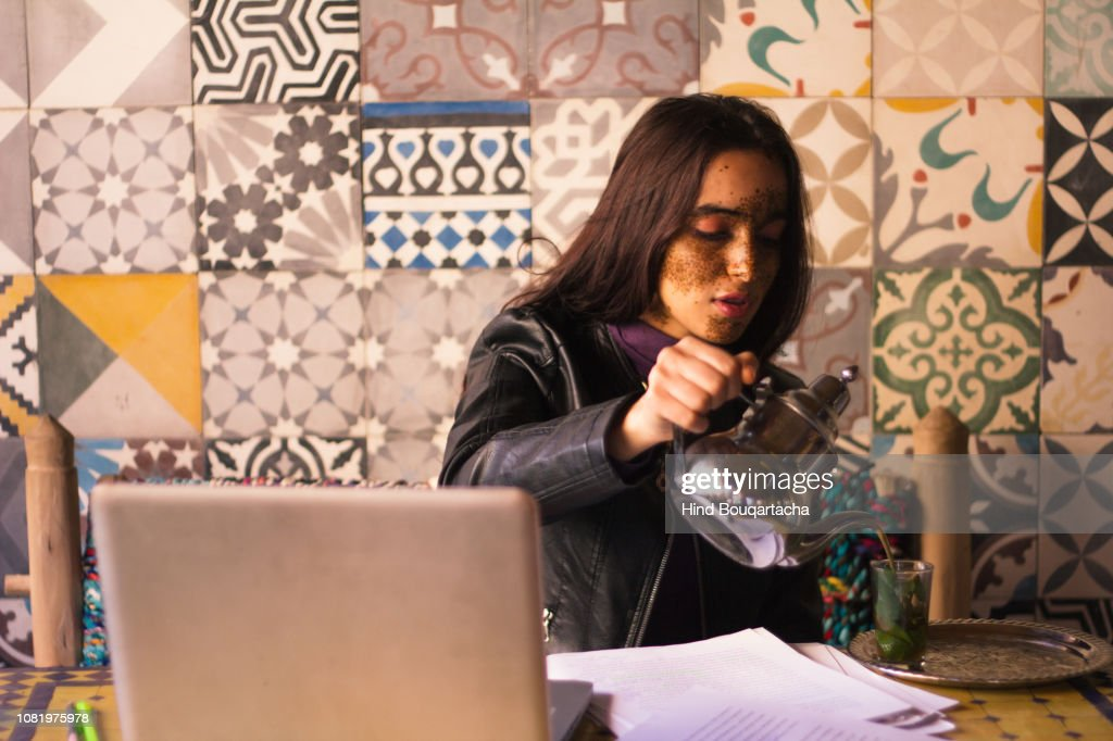 young women pouring tea front of her computer : Stock Photo