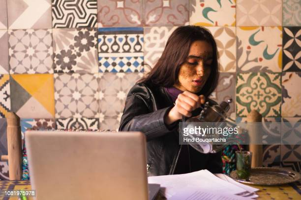 young women pouring tea front of her computer