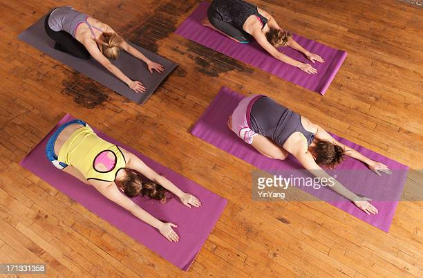 Young Women Practicing Child Pose Attending Group Yoga Workout Exercise