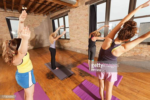 Young Women Practicing Stretching Exercise Attending Group Yoga Workout