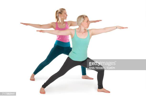 Young Women Practicing Warrior 2 Posture Against White Background