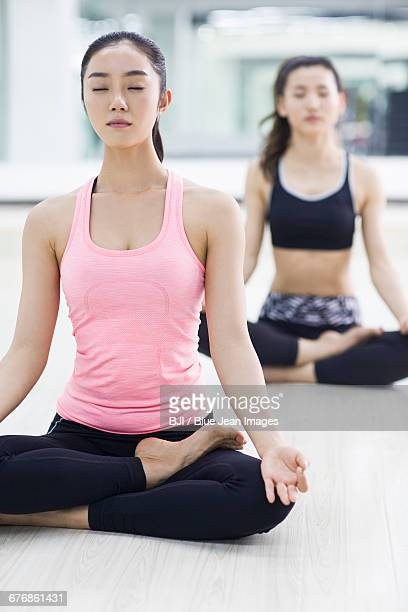 Young women practicing yoga at gym
