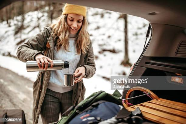 young women preparing for walking in snowy forest - flask stock pictures, royalty-free photos & images