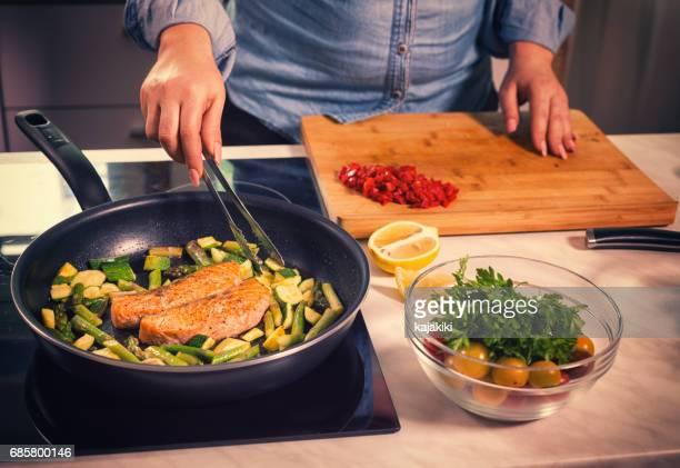 mulheres jovens em casa a preparar salmão - só uma mulher de idade mediana - fotografias e filmes do acervo