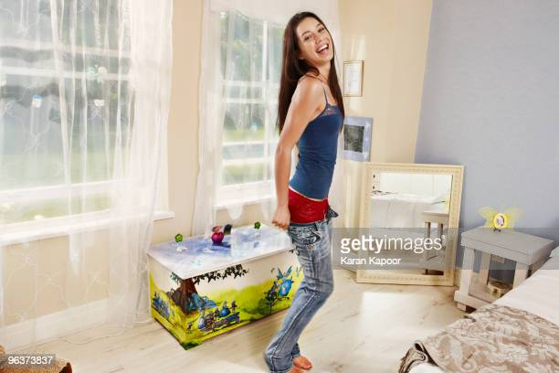 Young women pulling on jeans