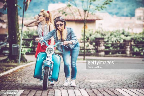young women pushing broken down motor scooter and calling for help - moped stock photos and pictures