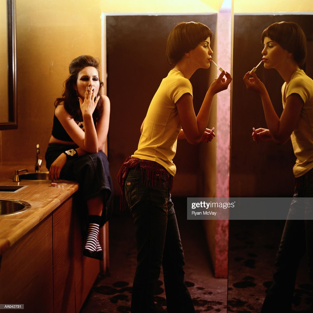 Young women putting on makeup in nightclub bathroom stock for Nightclub bathroom design