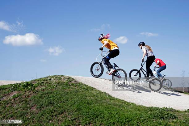 young women racing bmxs on racing track - bmx track london stock pictures, royalty-free photos & images
