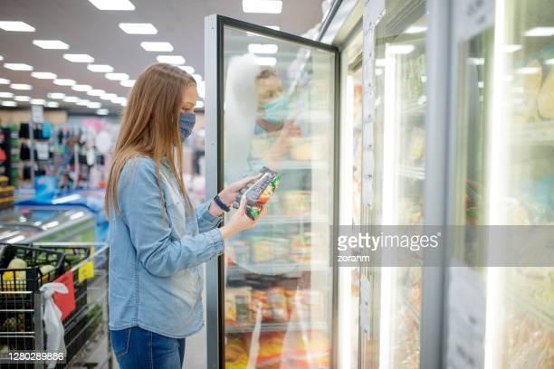 jeunes femmes lisant l'étiquette de nutrion sur les aliments congelés au milieu de l'éclosion de covide-19 - aliment surgelé photos et images de collection