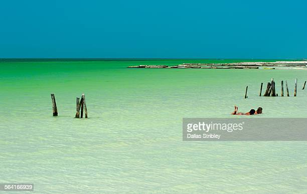Young women relax in the shallows of Holbox Island